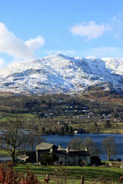 view of snowy hills across a lake with a farm in the foreground
